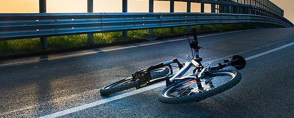 Bicycle laying on the side of the road