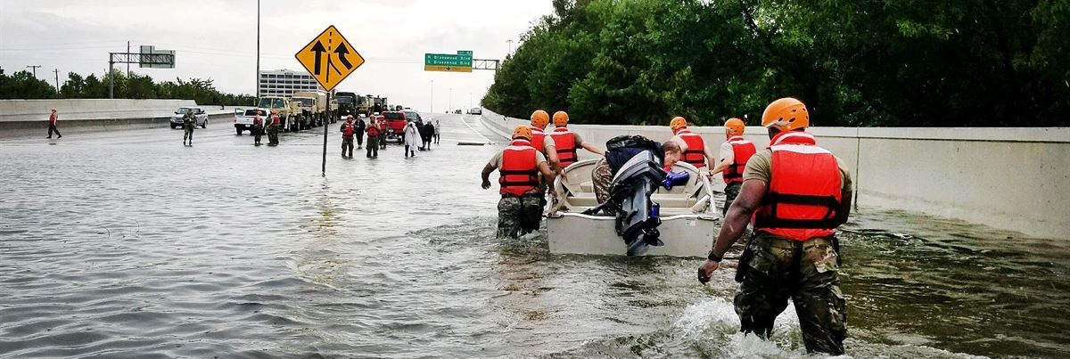 Hurricane Harvey flood rescue team with boat wading through knee-high water on flooded highway