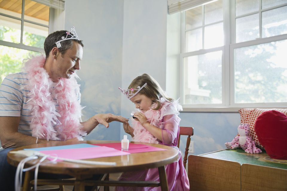 Little girl painting fathers fingernails at table
