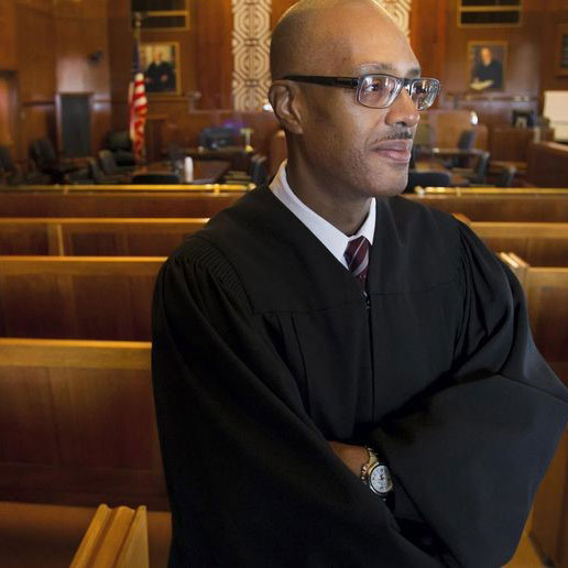 Judge standing in courtroom with arms crossed